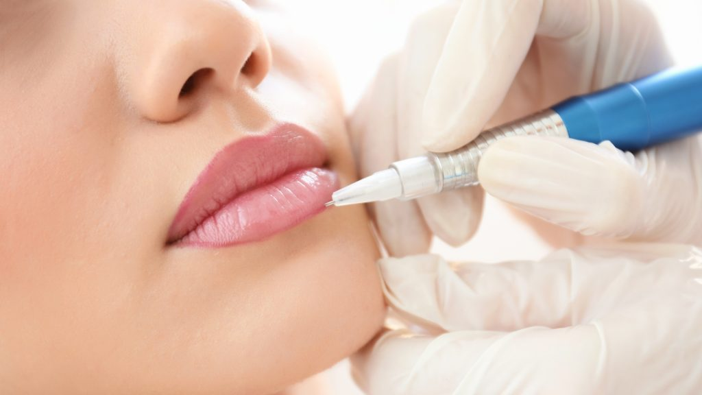 Young woman having permanent makeup on lips in beautician salon